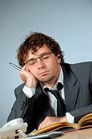 Bored young businessman sleeping in office