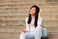 Brunette girl in casual listening music sitting on steps