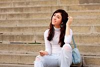 Brunette girl in casual listening music sitting on steps