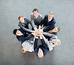 High angle view portrait of business people joining hands in circle (thumbnail)