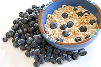 Blueberries outside a bowl of blueberries in milk and cereal isolated over a white background.