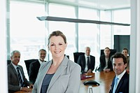 Portrait of smiling businesswoman and co_workers in conference room