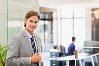 Portrait of smiling businessman with coffee cup