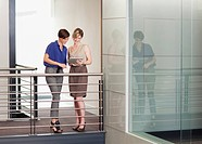 Businesswomen with digital tablet on elevated walkway in office (thumbnail)