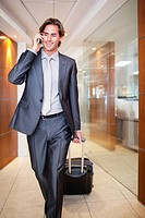 Businessman talking on cell phone and pulling suitcase (thumbnail)