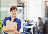 Portrait of smiling businesswoman holding binder in office