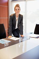 Portrait of smiling businesswoman leaning on table in conference room