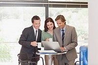 Business people drinking coffee at laptop