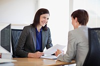 Businesswomen with paperwork talking face to face (thumbnail)