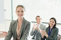 Co_workers clapping for smiling businesswoman