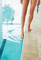 Woman dipping toe in swimming pool