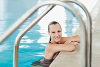 Portrait of smiling woman leaning on edge of swimming pool