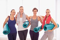 Portrait of smiling women holding yoga mats