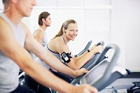 Portrait of smiling woman on exercise bike in gymnasium