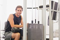 Portrait of smiling man using exercise equipment in gymnasium