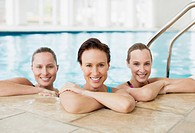 Portrait of smiling women leaning on edge of swimming pool