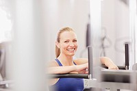 Portrait of smiling woman using exercise equipment in gymnasium
