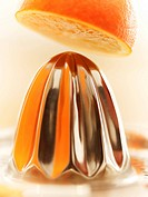 Close up of orange above juicer