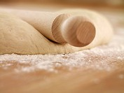 Close up of rolling pin on dough