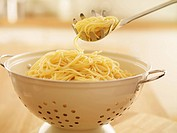 Close up of spoon scooping spaghetti in colander (thumbnail)