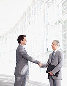 Smiling businessmen shaking hands in modern lobby