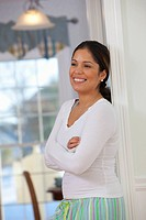 Hispanic woman standing with arms crossed and smiling