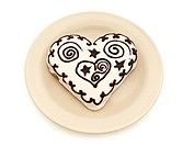 Photo of spice cake in heart shape in plate against white background