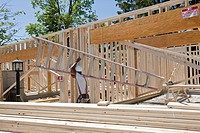 Carpenter carrying a ladder in a house being framed