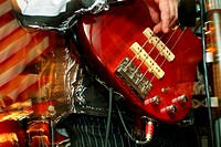The musician plays on red a bass_guitar