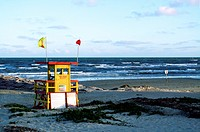 lifeguard station or stand on the beach as the sun is setting