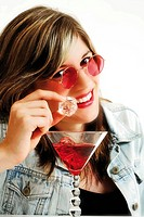 Young woman wearing pink sunglasses and drinking a red drink with an ice cube in her hand