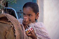 Girl applying a coloured bindi, Badami, Karnataka, South India, India, Asia