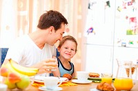 Young happy father and son having breakfast together