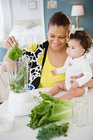 Mixed race mother holding baby and using blender