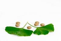 Ginkgo biloba leaf with pills on bright background.