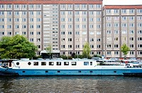 Boat on the Spree River in front of an apartment house on Schiffbauerdamm, Berlin, Germany, Europe