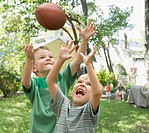 Caucasian boys playing football in backyard