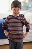 Caucasian boy grimacing with hands on hips