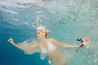 Caucasian bride in bikini swimming under water