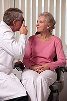 Ophthalmologist examining a womans eyes with a direct ophthalmoscope