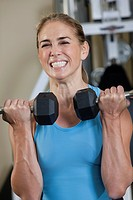 Woman exercising with dumbbells in a gym