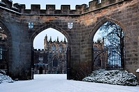 Bishop´s Palace: view of arched entranceway and forecourt, with chapel beyond, in late afternoon sunlight, winter with snow and blue sky, Bishop Auckl...