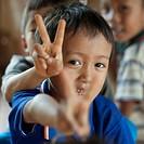 Close_up of Padaung boys showing V sign, Huay Pu Keng, Mae Hong Son Province, Thailand
