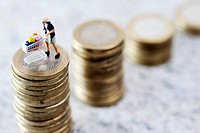Miniature figurines of a woman with a shopping cart on a coin stack, symbolic image for rising food prices