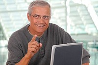 Middle aged man sitting at laptop computer and pointing at camera. Man is smiling and casually dressed. Horizontal format with blurred office backgrou...
