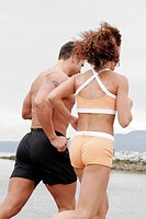 strong muscular couple running on the beach together. working out.