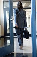 A young man walking through doorway