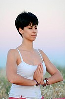 Attractive short haired woman practices yoga in nature