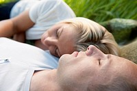 Man and woman sleep outdoors in a field of grass.