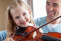Young girl plays the violin while her father looks on.